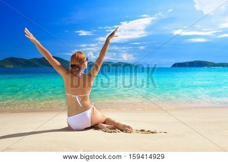 Pretty woman in a good mood sunning on the white sandy beach.