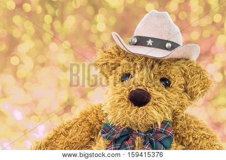Close up cowboy teddy bear with yellow bokeh background
