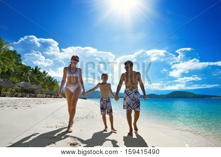 Happy family walks along the white sandy beach.