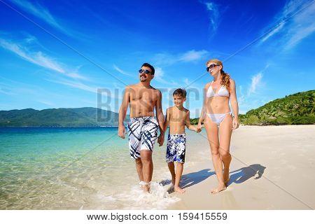 Happy family walks on sandy tropical beach shore