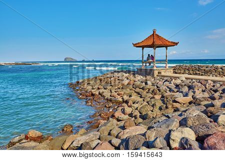 Couple Sitting In Traditional Balinese Gazebo