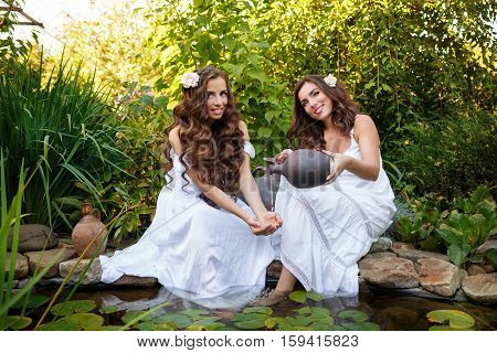 Two sisters in white dresses at the pond with water lilies. Girl pours water from earthenware jug on the old hands to her sister.