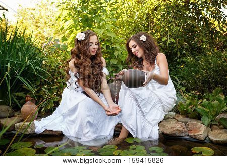 Two sisters in white dresses at the pond with water lilies. The girl pours water from a pitcher on the old hands to her sister.