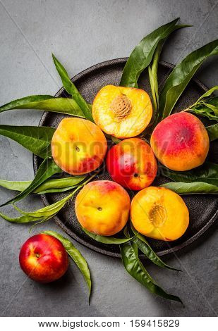 Fresh peaches with fresh leaves on black plate on gray stone slate background. Summer peaches top view