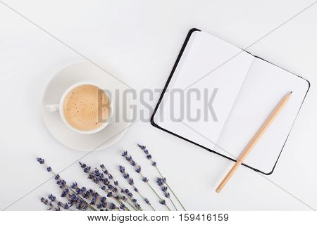 Coffee clean notebook and lavender flower on white table from above. Woman working desk. Cozy breakfast. Mockup. Flat lay style.