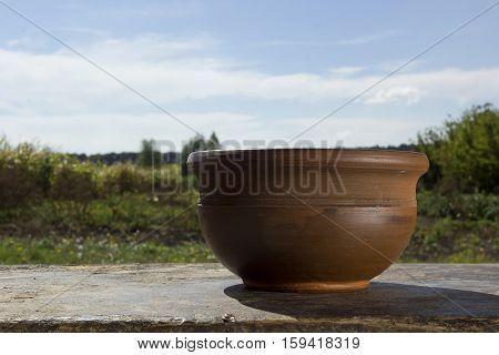 Brown ceramic pot on a background of the rural landscape