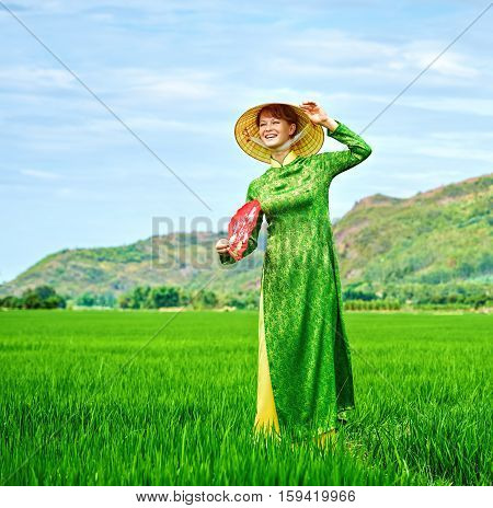 Girl in national Vietnamese dress is waving happily with the veer in the rice field.