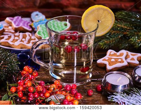 Christmas glass mug and Christmas multicolored cookies on form stars on plate with fir branches. Mug decoration lemon slice on wooden table. Christmas treats and candels.