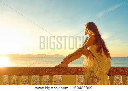 Romantic woman sit in a balcony and view sunrise