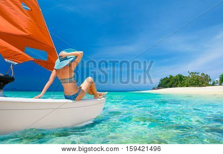 Woman traveler sit at the stern of boat at sunny day looking to the beach island. Indonesia