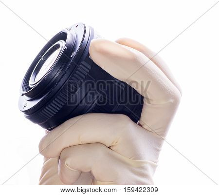 Hand and lens, side view. Lens camera in his hand, a hand in a white glove on a white background