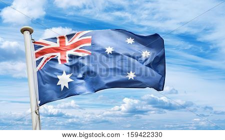 Australian flag blows in the wind against blue cloudy sky background