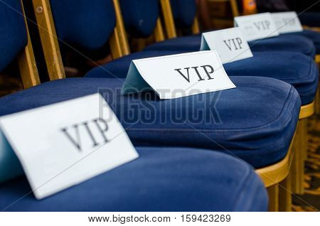 Paper label for VIP guests on a chair in a large hall
