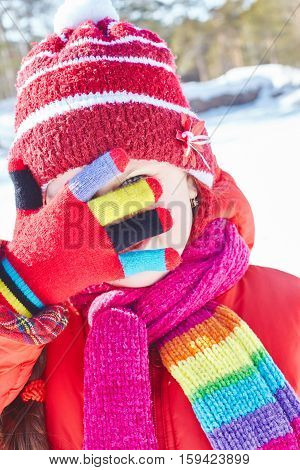 Girl hiding face with hand in winter