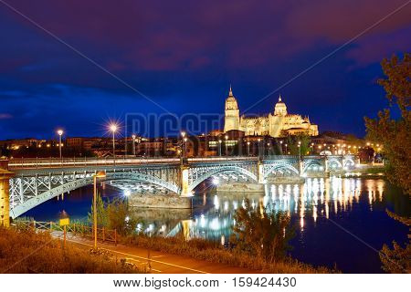 Salamanca skyline sunset in Enrique Estevan bridge over Tormes river in Spain