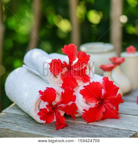 Spa Setting With Towels And Red Hibiscus Flowers