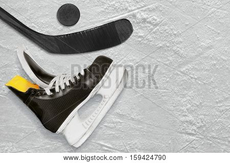 Black hockey stick skates and the puck on the ice. Texture background
