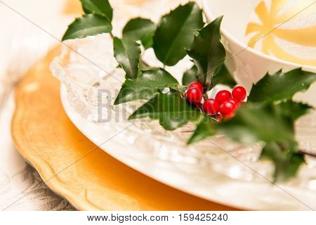 golden plates paired with crystal and holly makes this Christmas place setting festive.