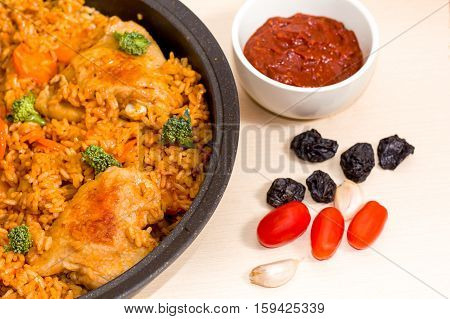 stewed chicken with rice, tomatoes, garlic, prunes, sauce