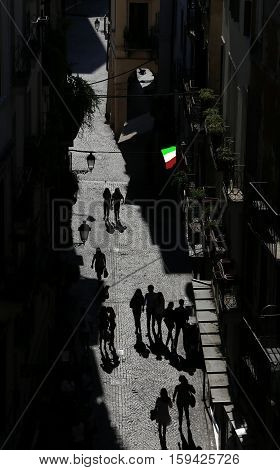 Italian flag and silhouettes of people in the narrow street of the city