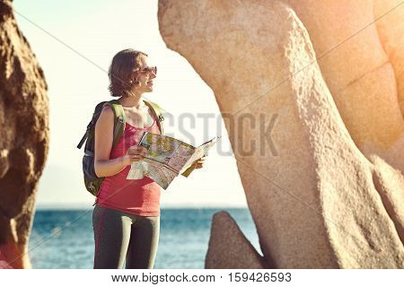 Young woman tourist standing near the rocks on the seashore reading the map. Traveling along Asia freedom and active lifestyle concept