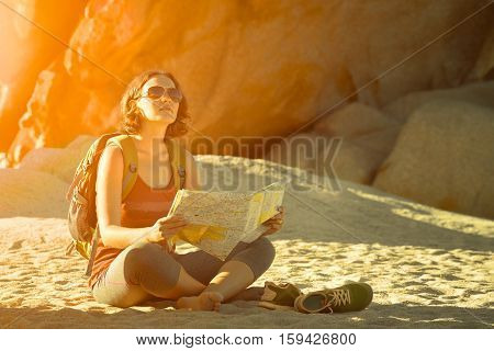 Young woman hiker sit and looking on mountain landscape. Traveling freedom and active lifestyle concept