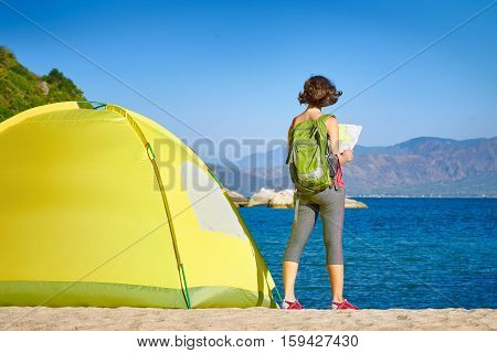 Back side of backpacker girl searching right direction on map Traveling along Asia freedom and active lifestyle concept
