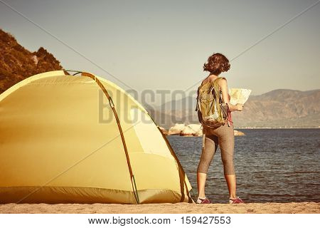 Back side of girl backpacker searching right direction on map Traveling along Asia freedom and active lifestyle concept