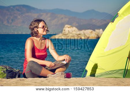 Young lady hiker sit near the tent and looking on sea landscape. Traveling freedom and active lifestyle concept