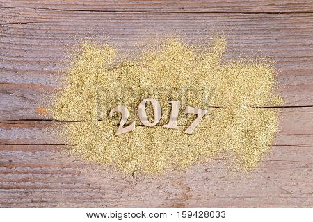 number 2017 on wooden background with golden glitter