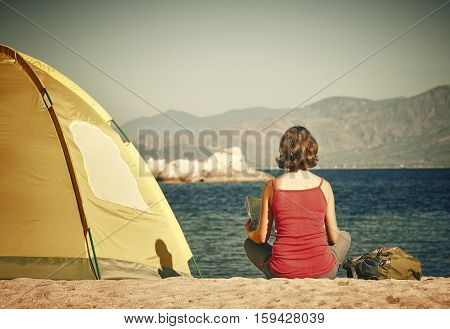 Young woman tourist sit near the tent looking the map and thinking about future boat tour