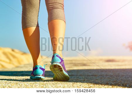 Runner feet running on road closeup on shoe. Woman fitness jog workout wellness concept.