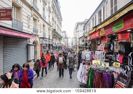 PARIS - FRANCE: MARCH, 16 2015:  Tourist and many souvenir shops on the way up to the Basilica Sacre Coeur in Montmartre, Paris, France