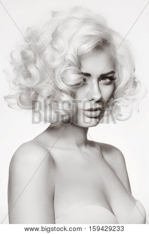 Black and white vintage style portrait of young beautiful glamorous woman with platinum blonde curly hair