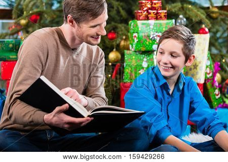 Daddy reading out from book for kid under X-mas tree on Christmas
