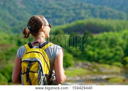 Young backpacker with a backpack enjoy the beautiful view. Camera focus on traveller