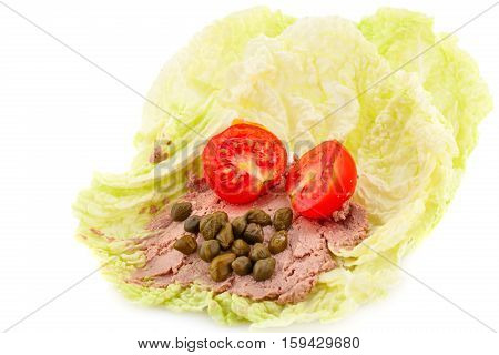 Meat pate with capers and tomato on lettuce leaves.