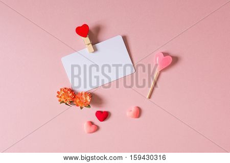 Valentine day composition: credit / visiting card template with clamp spring flowers candy and small hearts on light pink background. Top view.