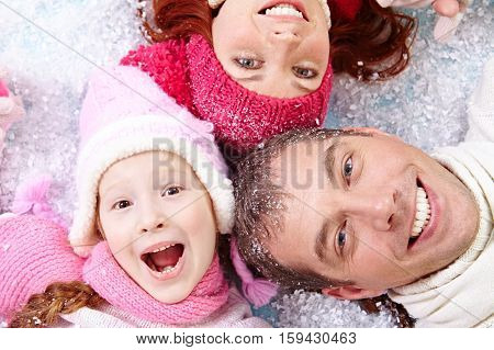 Faces of joyous family lying down on snow