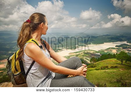 Hiker with backpack relaxing on top of the mountain. Ecotourism concept image with happy female hiker.