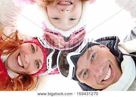 Directly below shot of positive family wearing ski goggles