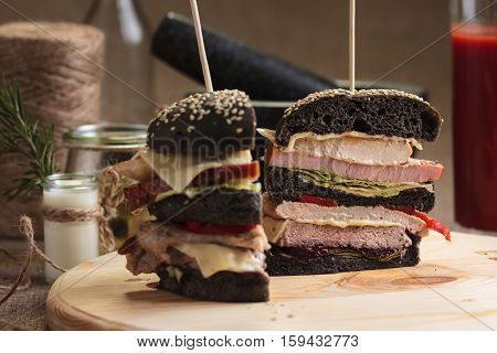 Trendy Burger With Four Meats In Black Bun Sliced