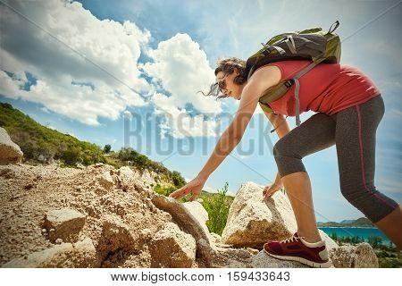 Hiker with backpack walking on a rocky terrain looking at beautiful landscape motivation and inspiration. Traveling along Asia active lifestyle concept