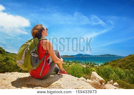 Young tourist with backpack relaxing on top of the mountain and enjoying beatiful coast view.. Ecotourism concept image with happy female hiker.