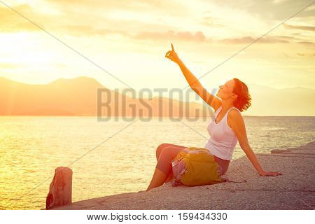 Young woman tourist sit at pier and dreams about future. Traveling along Asia freedom and active lifestyle concept