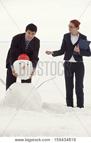 Strict business lady giving orders to manager making snowman
