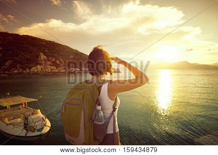 Young woman hiker standing on the coast and enjoying sunrise over the sea. Traveling along Asia active lifestyle concept