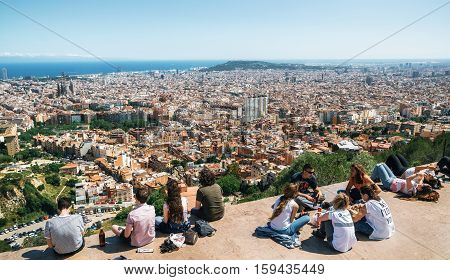 Barcelona Catalonia Spain - May 30 2015: Young people sit on the viewpoint communicate and look from the above of Barcelona city from Bunker El Carmel or Turo de la Rovira. Catalonia Spain.