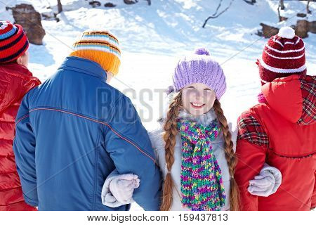 Portrait of cute smiling girl looking at camera while her friends standing back to the camera