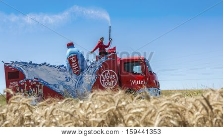 Saint-Quentin-FallavierFrance - July 16 2016: Vittel vehicle during the passing of Publicity Caravan in a wheat plain in the stage 14 of Tour de France 2016.Vittel is a French bottled water brand.